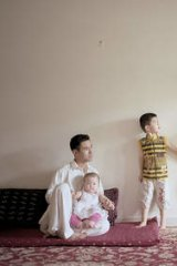 Hassan Rezayee holding his daughter Roshni, his wife Fatima and son Moeez.
