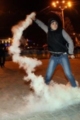 A pro-Ukrainian protester in Donetsk throws back a smoke bomb at pro-Russian protesters.