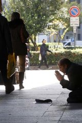A man begs for money in front of a bank in Milan, Italy, where borrowing rates have spiked.
