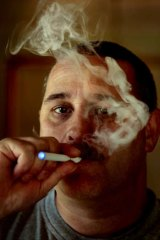 Melbourne man Terry Halmshaw smokes an e-cigarette that gives off harmless water vapour instead of smoke.