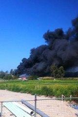 Smoke from the Richmond factory blaze engulfs nearby properties.