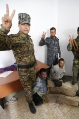 Shiite paramilitary fighters and Iraqi security forces arrest Islamic State militants in Tikrit this week.