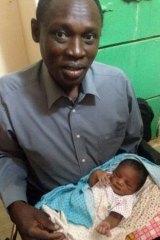 Daniel Wani carrying his newborn daughter Maya at the womens prison.