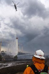 Firefighters on land and in a helicopter battle fire burning at the Hazelwood Coal Mine at Morwell, Australia.