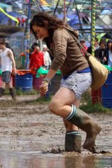 A gum-booted festival goer sloshes through the Glastonbury mud.
