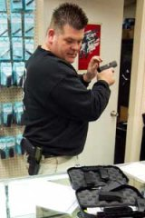 Greg Wolff takes a look at a customer's Glock semi-automatic pistol at his shop in Phoenix.