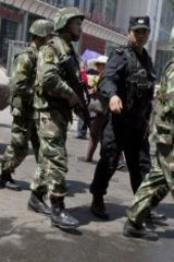 Ongoing violence: Armed Chinese paramilitary policemen march past the site of an explosion outside the Urumqi South Railway Station in Urumqi in north-west China in May.