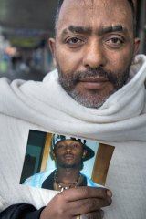Betachen Atakelt Seyoum with a picture of his son Michael.