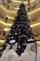 Two Emirate men look to a Christmas tree which has been decked out with dollars $11m worth of gold, at the Emirates Palace hotel, in Abu Dhabi, United Arab Emirates.