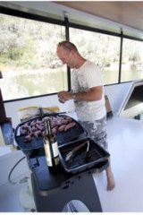 Noel Courtney upstairs on their Lake Eildon houseboat cooking a BBQ lunch.