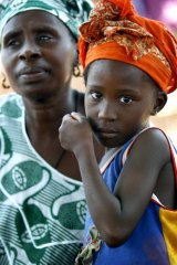 A young girl listens while her mother attends a meeting of women from several communities in Senegal that are eradicating female genital mutilation.