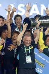 Japan's coach Alberto Zaccheroni raises the trophy as the team celebrates winning the East Asian Cup championship in Seoul on Sunday.