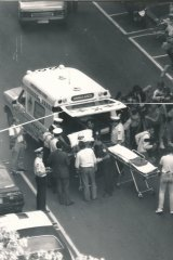 Ambulance workers and police surround a victim of the Queen Street Shooting before they're loaded into an ambulance.
