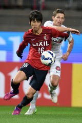 Shuto Yamamoto of Kashima Antlers gets to the ball ahead of Shannon Cole.