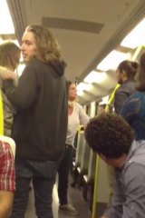 The woman, in white shirt and jeans, can be seen confronting a man of African background on the train.