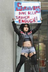 Carmen Chan holds up a sign in front of police headquarters in Toronto, Canada