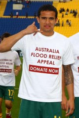 Tim Cahill poses with a t-shirt showing his support for the flood victims of Queensland.