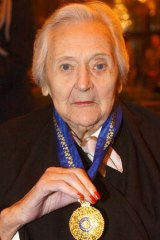 Nancy Wake displays her medal after she was made a Companion of the Order of Australia in London.