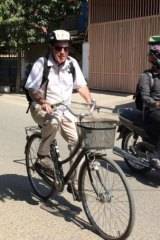 The writer hunched on a too-small bicycle as he practices on the back streets of Phnom Penh.