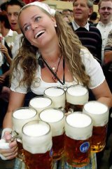 A waitress carries one-litre beer mugs during the opening day of Oktoberfest in Munich. <i>Photo: Reuters/Alexandra Winkler</i>