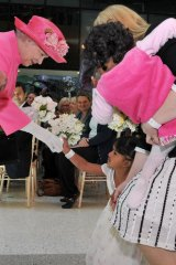 Her Majesty accepts a bouquet from former conjoined twin Trishna, guardian Moira Kelly holds Krishna.