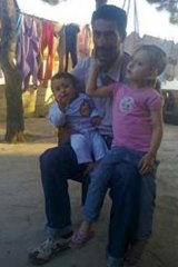 Broken Man: Hussein Khodor, with two of his eight children, all of whom died.