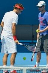 Roger Federer speaks to coach Stefan Edberg during a practice session.