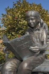 Bronze statues, including one of a young girl reading <i>To Kill a Mockingbird</i> are on the grounds of the old Monroe County Courthouse in Monroeville, Alabama.