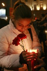 A Russian holds candles and flowers in memory of the victims of a blast near the Lubyanka metro station in Moscow.