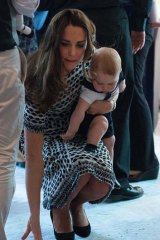 The Duchess of Cambridge picks up a doll after Prince George threw it.
