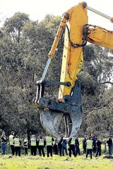 A tree harvester rests, while police stand ready to arrest Frankston Bypass protesters.