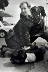 Daily grind: Constable Glenn Pullin arrests a man outside the roller skating rink in Noble Park in 1992.