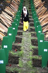 Muslim women inspect the graves prepared for newly identified victims.