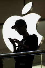 A man uses an iPhone in front of the Apple store in Hong Kong.