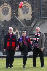 Game on... Perth Archbishop Roger Herft lets rip with a punt,  watched by Melbourne Archbishop Philip Freier (left) and the Auxiliary Archbishop of Melbourne Paul White (right).