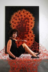 Anna Schwartz on an orange wire chair designed by the Campana brothers.