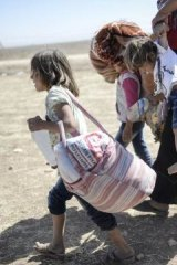 Syrian Kurds carry their belongings across the border into Turkey. Tens of thousands have fled the advance of Islamic State.