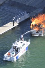Rescuers fight the boat fire at Woodman Point.