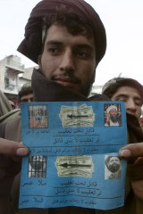 "An Afghan shows leaflets dropped by US  planes along the Afghan-Pakistan border in March 2003 reading ""Chase Murderers"" and naming Osama bin Laden and Mullah Omar. Doubts later emerged over whether the second picture was indeed Mullah Omar's."