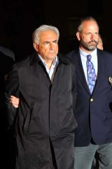 A handcuffed Dominique Strauss-Kahn (left) is taken from a police station in New York. Strauss-Kahn was charged Sunday with attempting to rape a New York chambermaid.