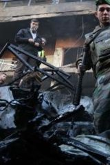 Lebanese soldiers and civilians inspect the scene of an apparent suicide car bombing in Beirut.