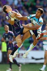Melbourne fullback Billy Slater leaps high to defuse a bomb against Gold Coast.