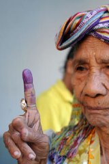 Democratic process ... an East Timorese woman shows her inked finger at a polling centre in Dili on Monday.