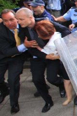 Prime Minister Julia Gillard is dragged away by her close protection team police to her car.