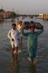 Villagers displaced from their homes by flooding make their way through flood waters in Punjab, Pakistan, earlier this year.
