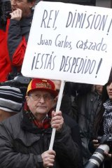 """A protestor holds a banner reading """"King, abdication! Juan Carlos, caught. You are fired!"""" outside the exit of a hospital from which King Juan Carlos was discharged."""