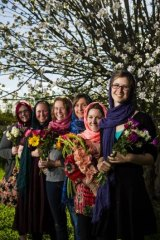 With love: Rebecca Bull, Kirrily Burnett, Eliza Spencer, Annabelle Lee, Gemma White and Hannah Dungan wore hijabs and gave out flowers at a Islamic service on weekend at a Muslim service.