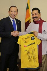 Prime Minister Tony Abbott gives Sri Lanka's President Mahinda Rajapaksa a signed Australian Rugby Union jersey in Colombo.