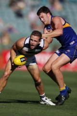 Joel Selwood of the Geelong Cats gets tackled by Jeremy McGovern of the West Coast Eagles.