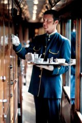 A cabin steward delivers afternoon tea to a compartment on Europe's famed luxury train service, the Orient Express.